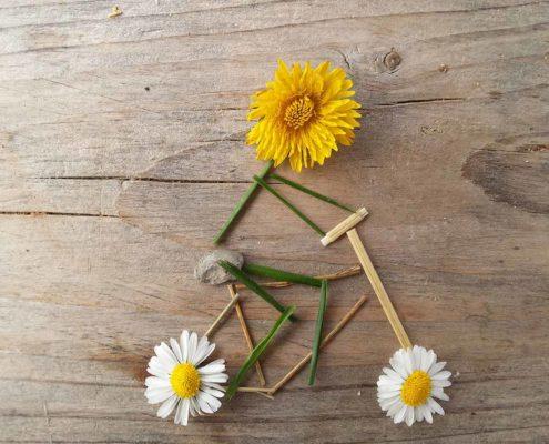 Fahrradfahrer aus Gras, Gänseblümchen und Butterblume